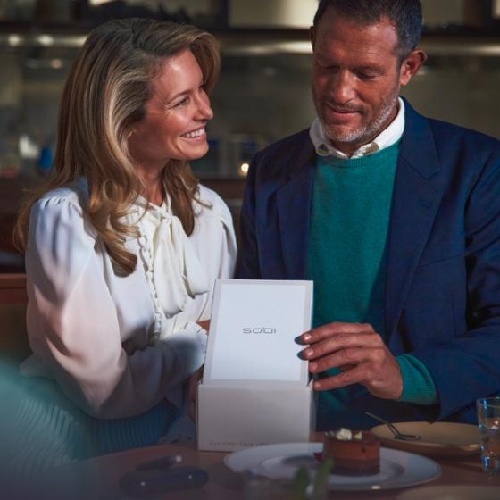 Ένας άντρας και μία γυναίκα ανοίγουν μία συσκευασία IQOS