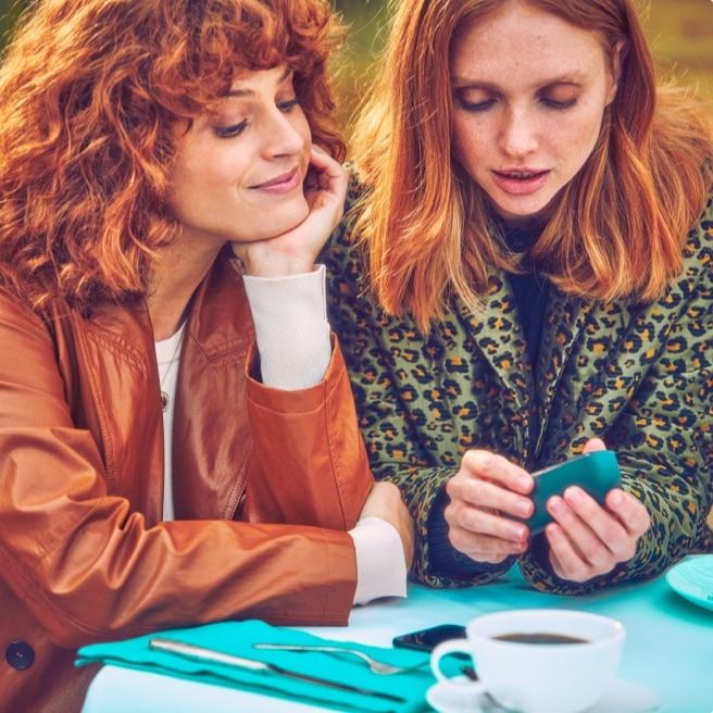 Two women looking at an IQOS device